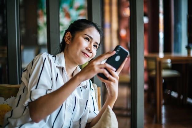 Frau, die ihr intelligentes telefon am café sitzt und spielt Kostenlose Fotos