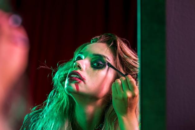 Frau, die ihr make-up im spiegel repariert Kostenlose Fotos