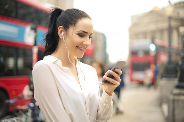 Frau, die ihr telefon beim hören mit kopfhörern verwendet Premium Fotos