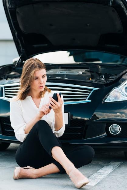 Frau, die ihr telefon und schwarzes auto überprüft Kostenlose Fotos