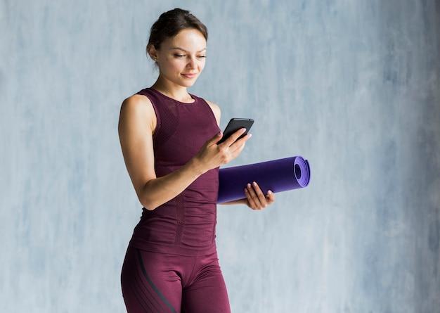 Frau, die ihr telefon während ihres trainings betrachtet Kostenlose Fotos