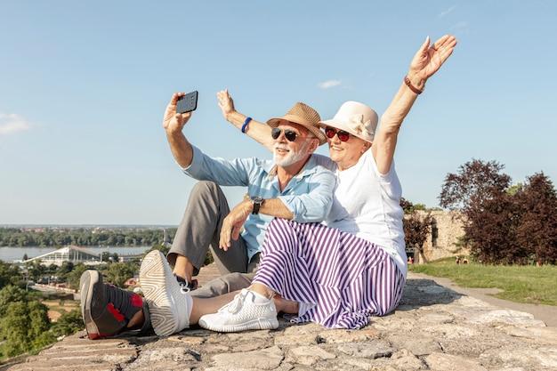 Frau, die ihre hände beim nehmen eines selfie anhebt Premium Fotos