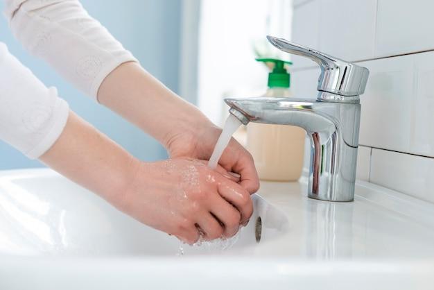 Frau, die ihre hände drinnen wäscht Kostenlose Fotos