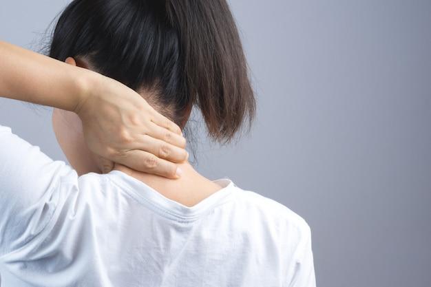 Frau, die ihre hand für nacken- oder dornschmerz setzt Premium Fotos