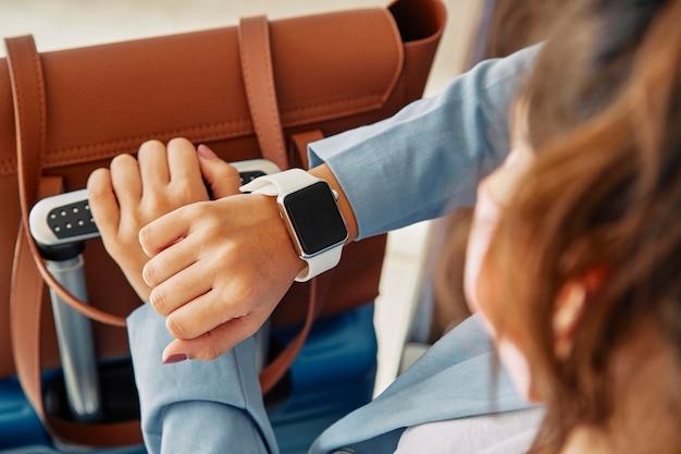 Frau, die ihre smartwatch während am flughafen während der pandemie betrachtet Premium Fotos