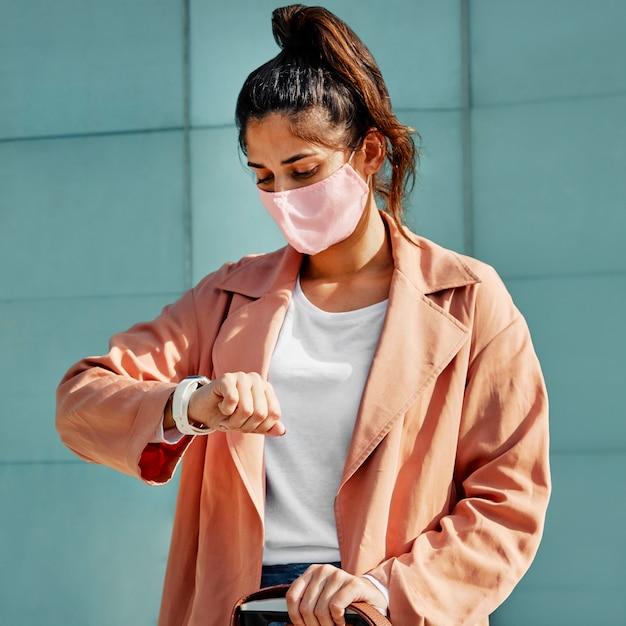 Frau, die ihre uhr beim tragen einer medizinischen maske während der pandemie am flughafen betrachtet Kostenlose Fotos