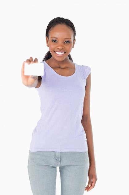 Frau, die ihre visitenkarte auf weißem hintergrund darstellt Premium Fotos