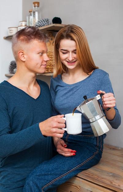 Frau, die ihrem freund etwas kaffee gießt Kostenlose Fotos