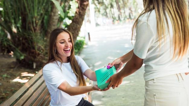 Frau, die ihrem glücklichen freund im park geschenk gibt Kostenlose Fotos
