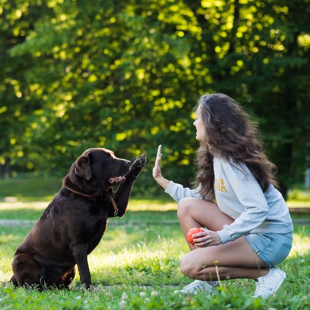 Frau, die ihrem hund hoch fünf gibt Kostenlose Fotos