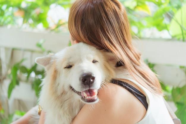 Frau, die ihren großen hund, glück und freundschaft ihrer hundefreundlichen haustiernahaufnahme umarmt Premium Fotos