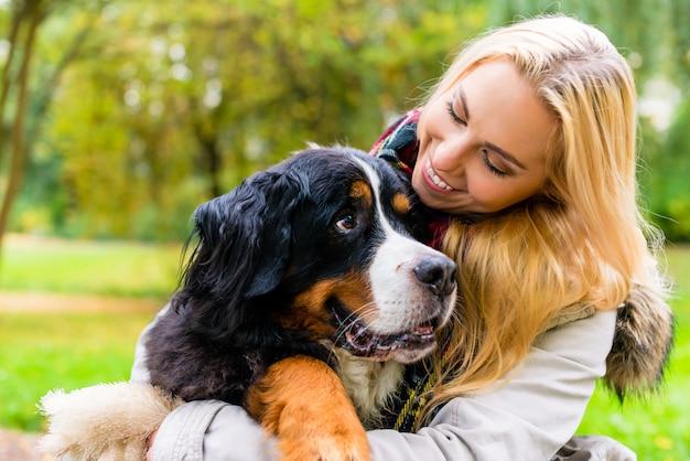Frau, die ihren hund im herbstpark umfasst Premium Fotos