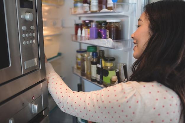 Frau, die ihren kühlschrank überprüft Premium Fotos