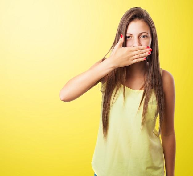 Frau, die ihren mund in einem gelben hintergrund Kostenlose Fotos