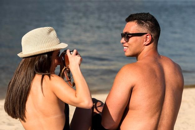 Frau, die ihren partner am strand fotografiert Kostenlose Fotos