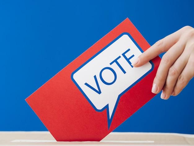 Frau, die ihren stimmzettel in den wahlkasten legt Kostenlose Fotos