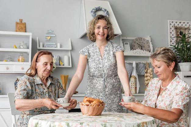 Frau, die ihrer mutter und oma in der küche kaffeetasse gibt Kostenlose Fotos