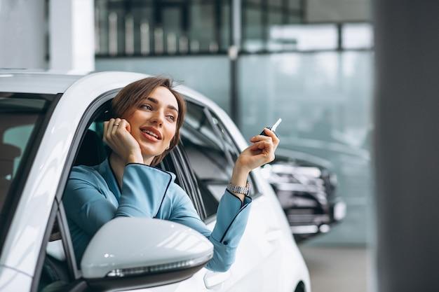 Frau, die im auto hält schlüssel sitzt Kostenlose Fotos