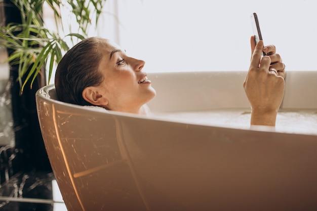 Frau, die im bad mit blasen entspannt und am telefon spricht Kostenlose Fotos