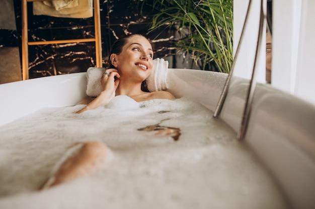 Frau, die im bad mit blasen entspannt Kostenlose Fotos