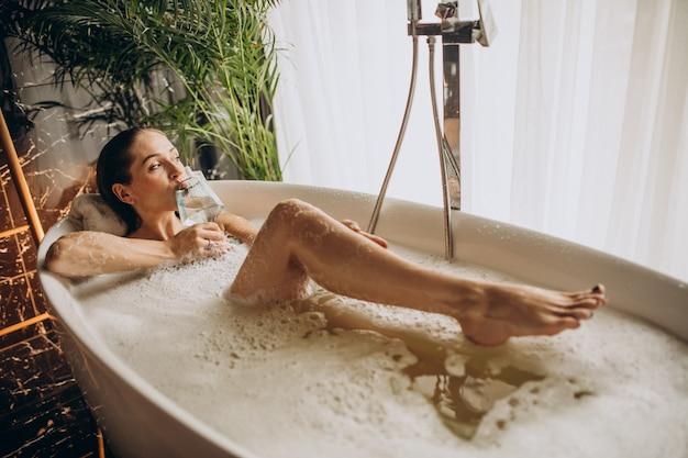 Frau, die im bad mit blasen und wein trinkt Kostenlose Fotos
