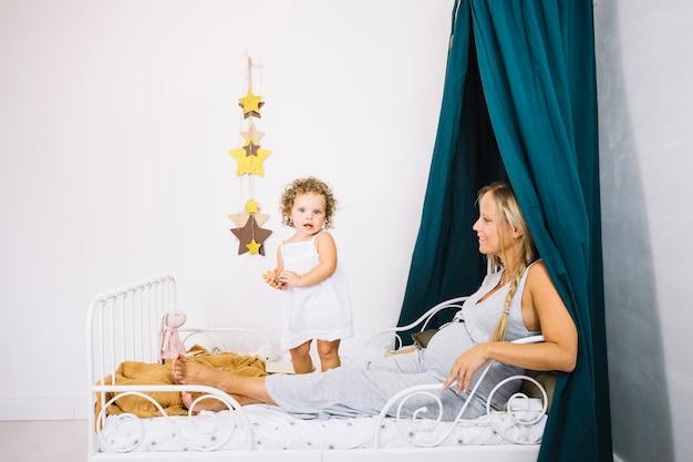 frau die im bett nahe baby stillsteht download der kostenlosen fotos. Black Bedroom Furniture Sets. Home Design Ideas