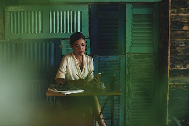 Frau, die im café sitzt, smartphone betrachtet und in notizbuch schreibt Kostenlose Fotos