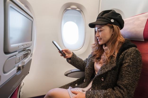 Frau, die im flug smartphone in der flugzeugzeit verwendet. Premium Fotos