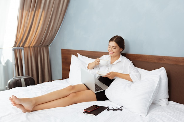 Frau, die im hotelzimmer arbeitet Premium Fotos