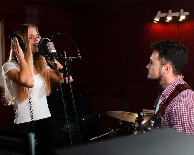 Frau, die im mikrofon und im kerl spielt gitarre singt Kostenlose Fotos