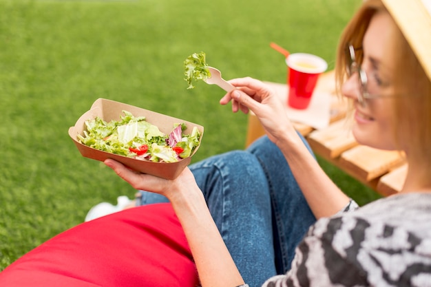 Frau, die im park lächelt und isst Kostenlose Fotos
