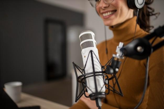 Frau, die im radio beim lächeln sendet Kostenlose Fotos