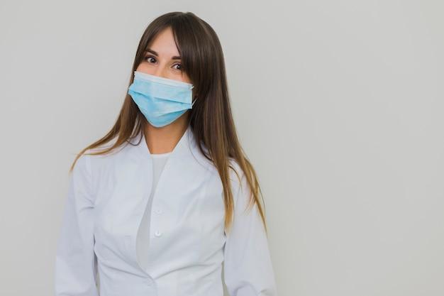 Frau, die im raum der chirurgischen maske und der kopie aufwirft Kostenlose Fotos
