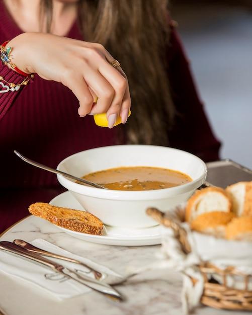 Frau, die im restaurant zitronensaft in linsensuppe zusammendrückt Kostenlose Fotos