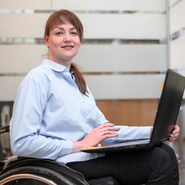 Frau, die im rollstuhl mit laptop sitzt Kostenlose Fotos