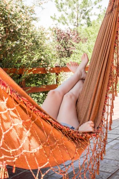 Frau, die in der hängematte auf terrasse liegt Kostenlose Fotos