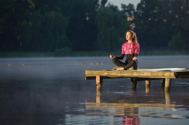 Frau, die in der natur auf dem fluss meditiert. yoga Premium Fotos