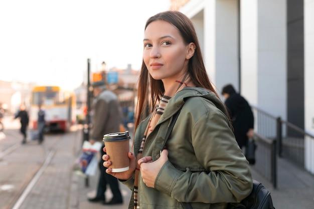 Frau, die in der seitenansicht der straßenbahnstation wartet Kostenlose Fotos