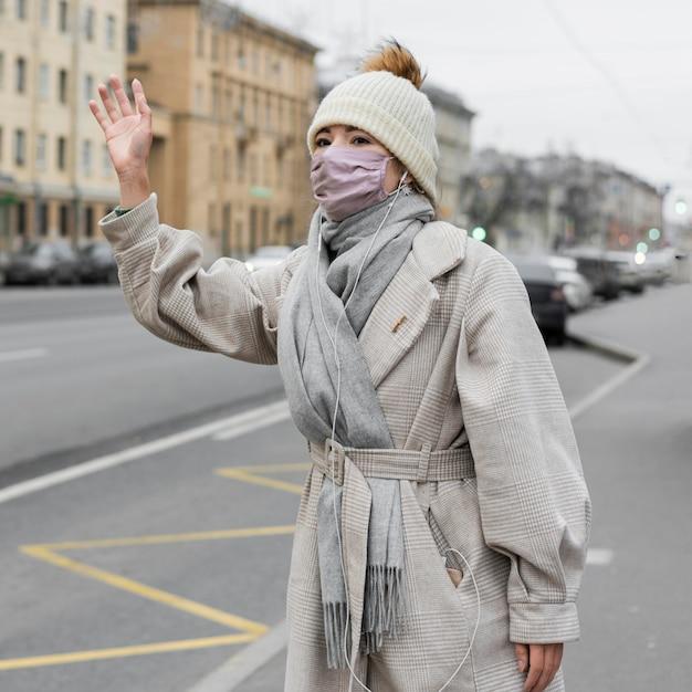 Frau, die in der stadt beim tragen der medizinischen maske winkt Kostenlose Fotos