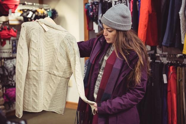 Frau, die in einem kleidergeschäft einkauft Kostenlose Fotos