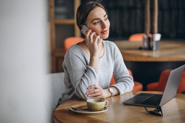 Frau, die in einem trinkenden kaffee des cafés sitzt und an einem computer arbeitet Kostenlose Fotos