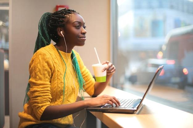 Frau, die in einer bar zu mittag isst, musik hört und ihren laptop verwendet Premium Fotos