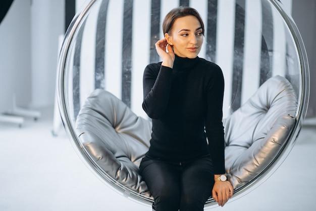 Frau, die in hängendem glasstuhl sitzt Kostenlose Fotos