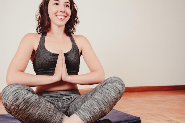 Frau, die in halber lotoshaltung sitzt. Premium Fotos