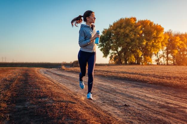 Frau, die in herbstfeld bei sonnenuntergang läuft. gesundes lebensstilkonzept. aktive sportliche menschen Premium Fotos