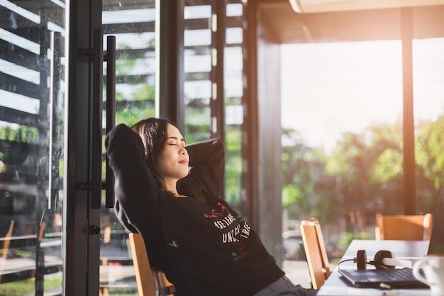 Frau, die in ihrem stuhl sich entspannt und die ansicht vom bürofenster genießt Premium Fotos