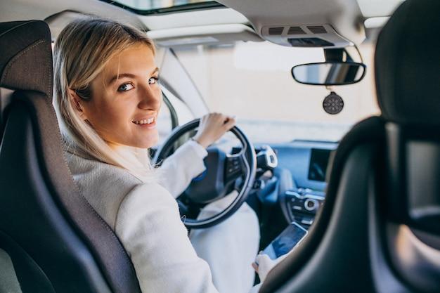 Frau, die innerhalb des elektroautos bei der aufladung sitzt Kostenlose Fotos