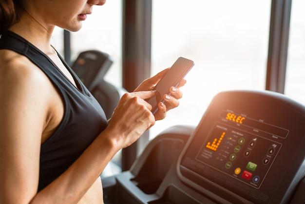 Frau, die intelligentes telefon wenn trainings- oder stärketraining an der eignungsturnhalle verwendet Premium Fotos