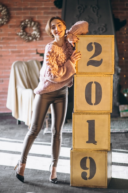 Frau, die kästen 2019 auf weihnachten bereitsteht Kostenlose Fotos