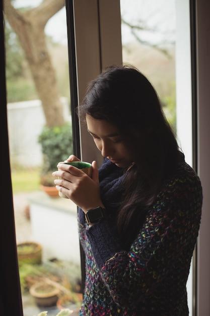 Frau, die kaffee nahe fenster zu hause hat Kostenlose Fotos